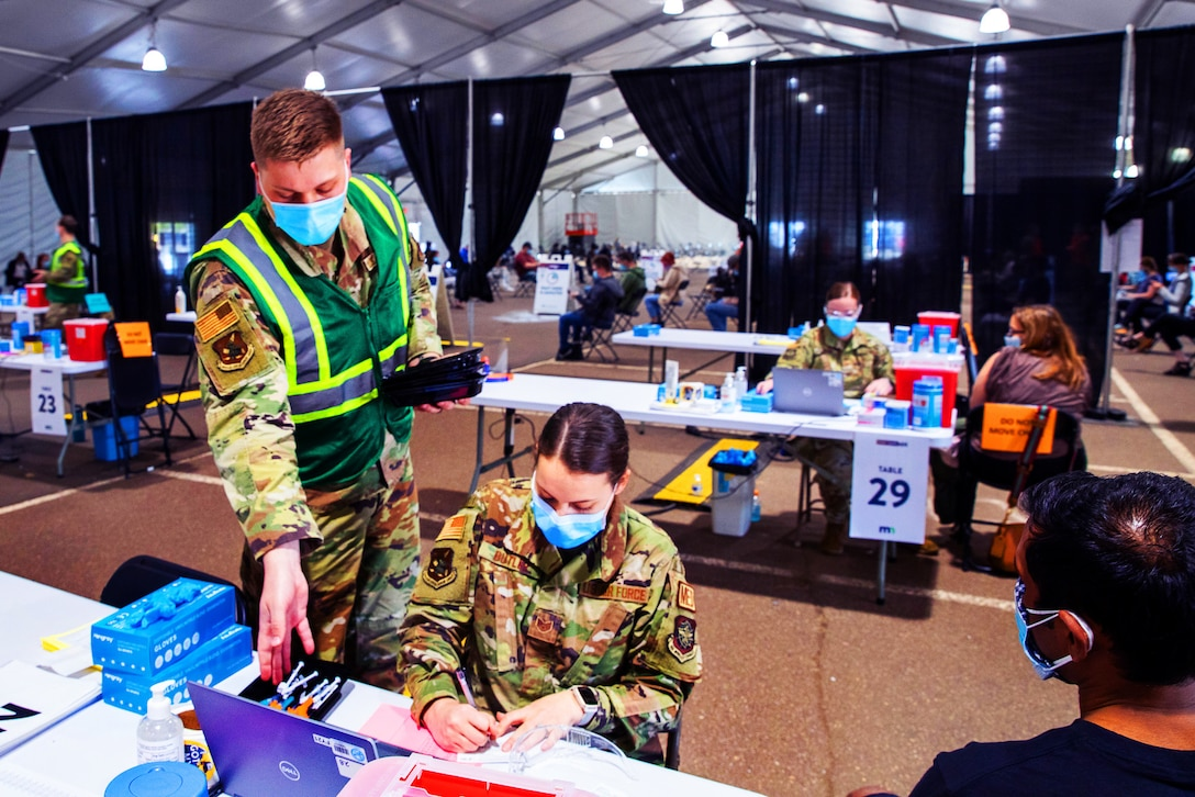Under a large tent, an airman wearing a face mask stands next to another airman wearing a face mask and seated at a table.