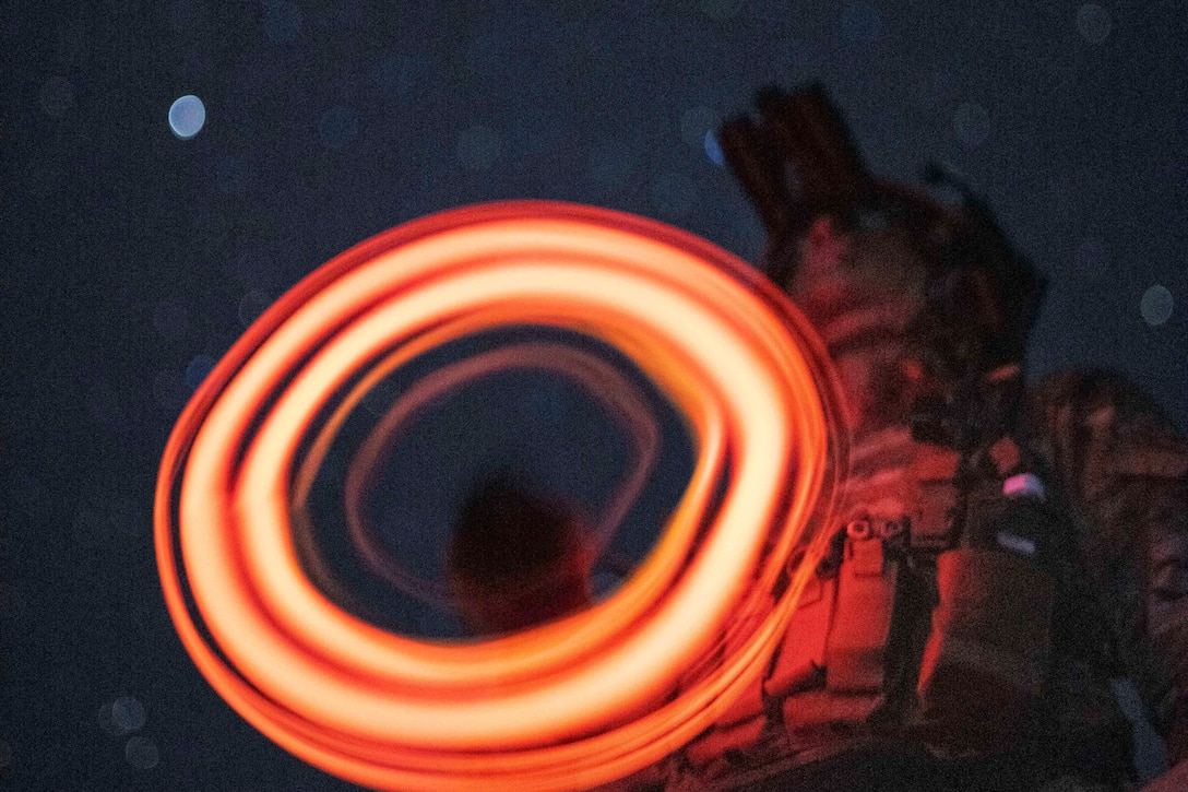 A soldier uses a circular light under a starry sky.