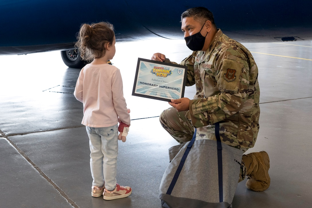 A kneeling airman presents a certificate to a small child.