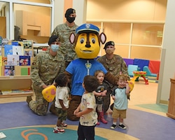 Members of the 14th Security Forces Squadron and their mascot, Chase the dog, pose for a photo with children at the Child Development Center, May 11, 2021, on Columbus Air Force Base, Mississippi. Columbus AFB had several events to show appreciation to the 14th Security Forces Squadron for National Police Week. (U.S. Air Force photo by Elizabeth Owens)