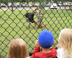 Children at the Child Development Center watch as Dixi, military working dog, and her handler showcase their skills, May 11, 2021, on Columbus Air Force Base, Mississippi. Working dogs are able to detect the scent of explosives, allowing for a more accurate and quick search of an area. (U.S. Air Force photo by Elizabeth Owens)