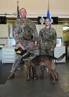 U.S. Air Force Master Sgt. Dustin Weeks, 14th Security Forces Squadron and Staff Sgt. Amber James, 14th Security Forces Squadron Military Working Dog handler, stand with Military Working Dog Ooleg #W136 during the K-9's retirement ceremony, May 14, 2021, on Columbus Air Force Base, Miss. Weeks presented Ooleg his final bone as a symbol of his final reward, while on active duty. (U.S. Air Force photo by Airman 1st Class Jessica Haynie)