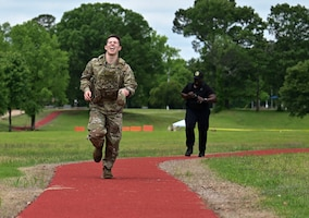 U.S. Air Force Airman Steele Falsetto, 14th Security Forces Squadron entry controller, sprints to the finish line during a Battle of the Badges competition, May 12, 2021, on Columbus Air Force Base, Miss. Falsetto was cheered on by the awaiting crowd as he crossed the finish line. (U.S. Air Force photo by Airman 1st Class Jessica Haynie)