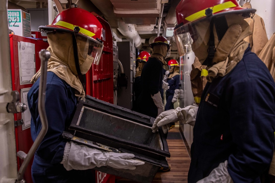Sailors prepare to fight a simulated fire.