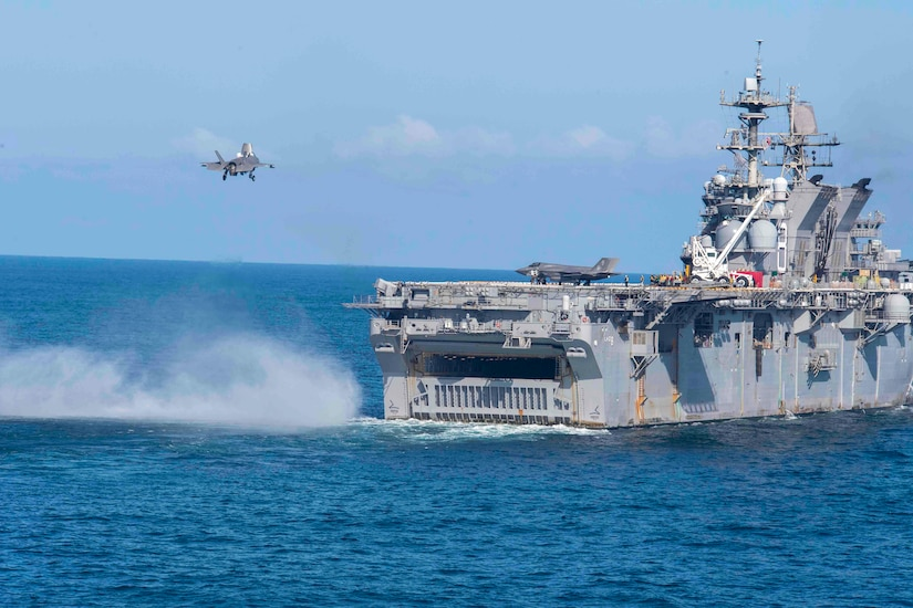 A jet prepares to land on a ship.