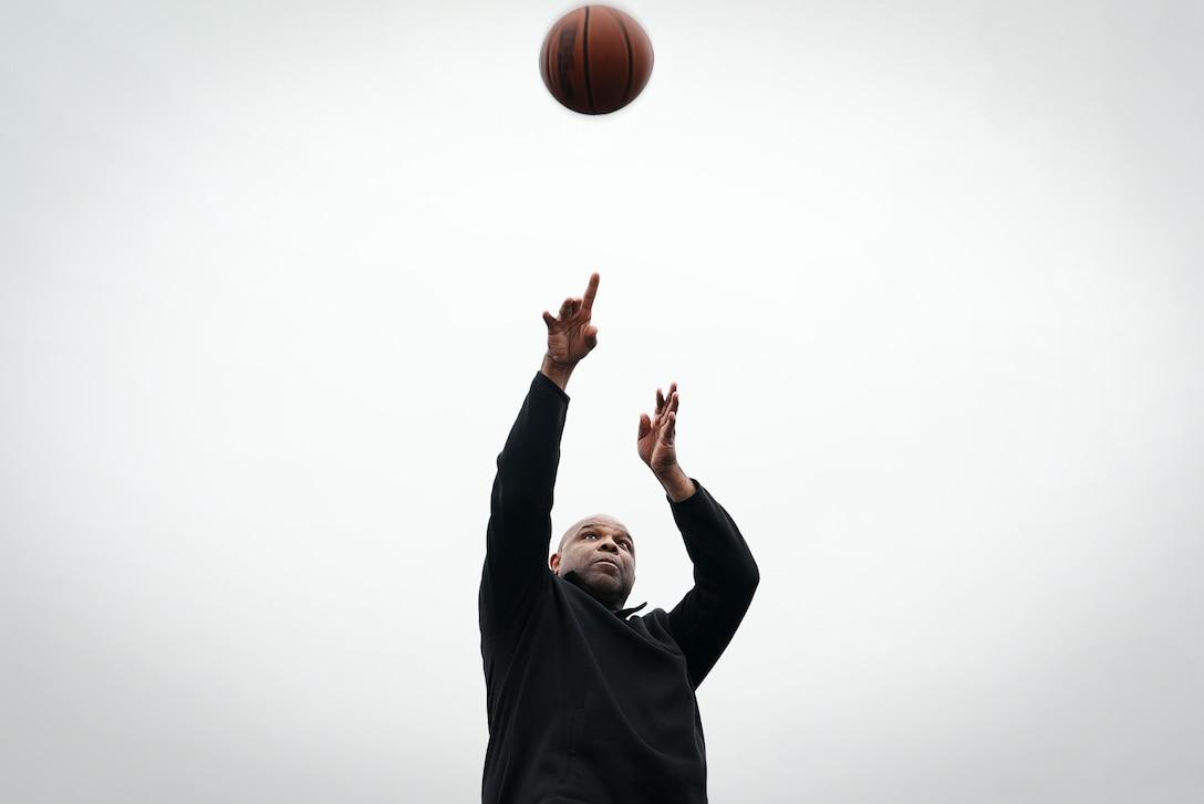 Civilian man throws basketball into air.