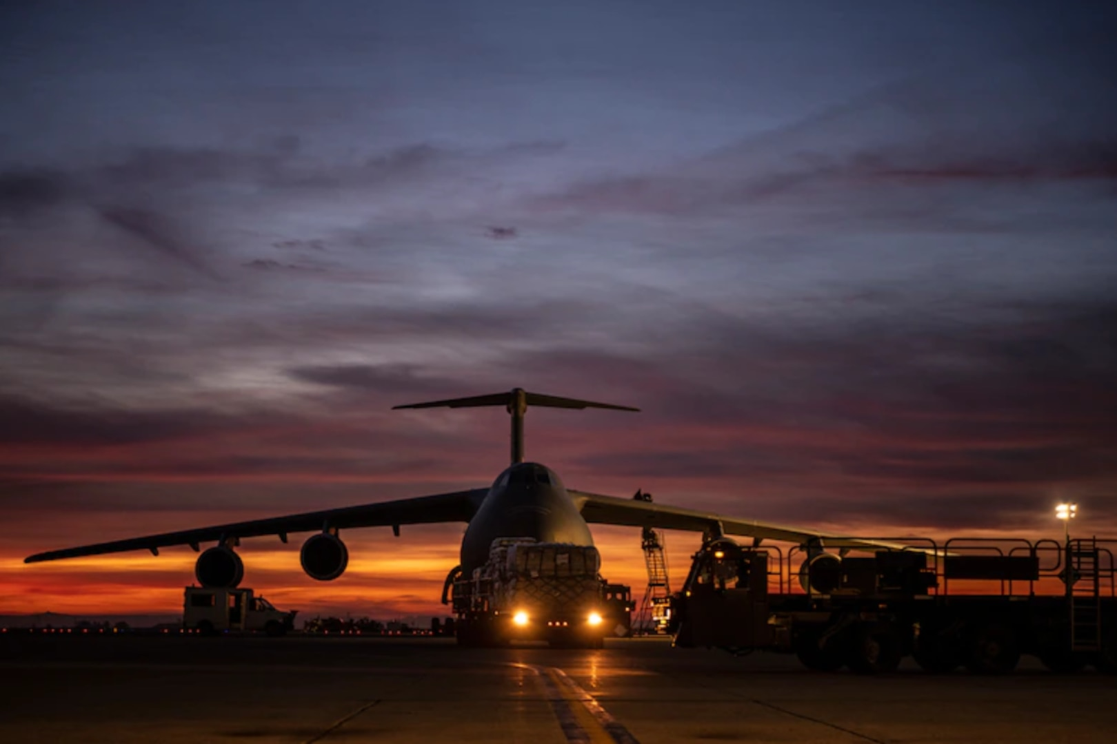 Airmen from the 60th Aerial Port Squadron load pallets holding lifesaving COVID-19 supplies onto a C-5M Super Galaxy at Travis Air Force Base, California, April 30, 2021.