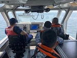 USCG instructor provides boat handling and navigation training to PCG students.
