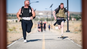 Senior Airman Douglas Ryan and Staff Sgt. Jake Harris, both of the 412th Security Forces Squadron race to the finish line during the Annual Police Week Run/Ruck/Walk Event at Edwards Air Force Base, California, May 10. (Air Force photo by Giancarlo Casem)