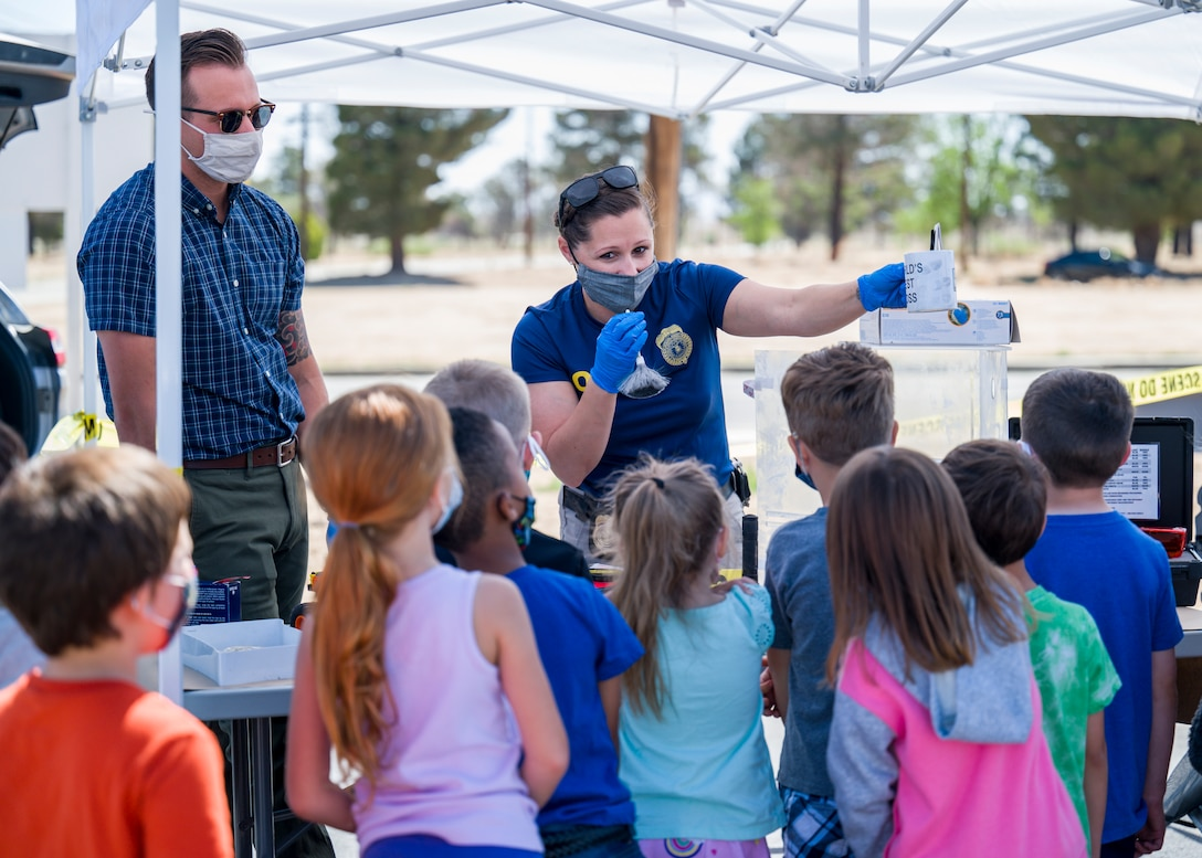 Office of Special Investigations agents show Bailey Elementary School students how they obtain fingerprints during Police Week 2021 at Edwards Air Force Base, California, May 11. (Air Force photo by Giancarlo Casem)
