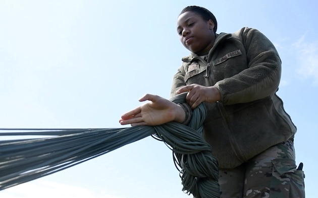 a woman daisy chaining parachute lines