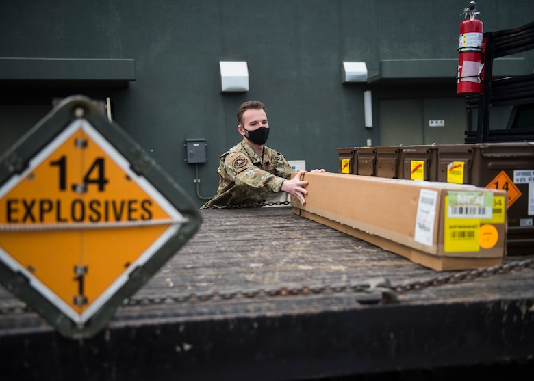 Man in uniform moves boxes of f-35 egress parts onto a truck bed for transportation.