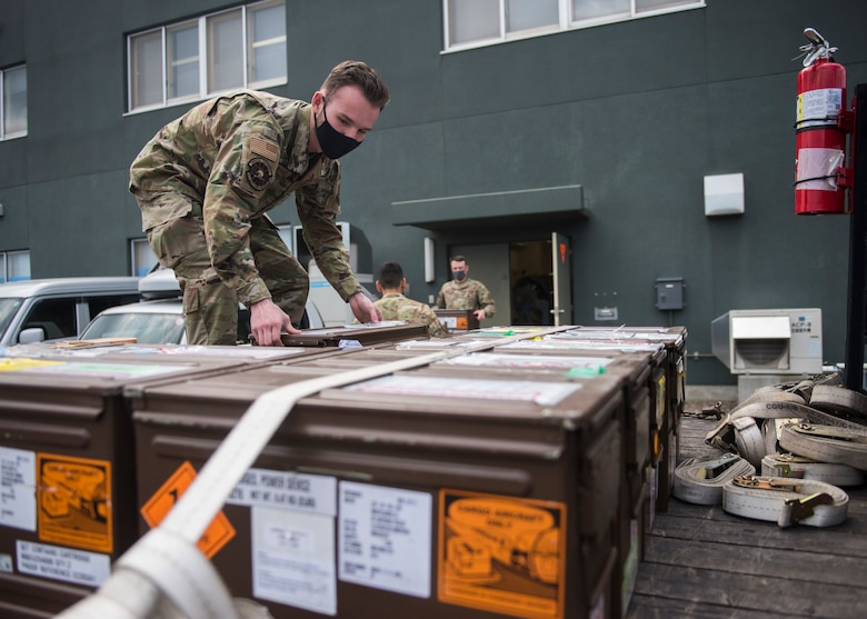 Man in uniform places boxes of F-35 egress parts down onto a truck bed.