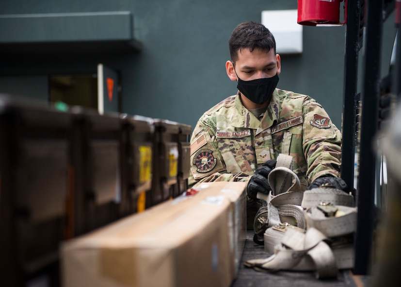 Man in military uniform grabs ropes to secure shipment of F-35 parts.