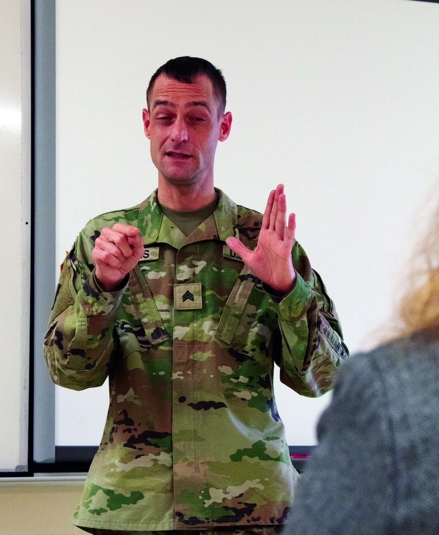 Michigan Army National Guard Sgt. Bill Fitrakis, 1460th Transportation Company, certified in American Sign Language, explains the COVID-19 vaccine process during a vaccination clinic at the Marine City Middle School in Marine City, Michigan, April 27, 2021. Due to most of sign language being a visual language, he cannot wear a mask as it would not impart the message.