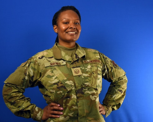 A woman in an Air Force uniform holds up a patch with the first sergeant rank.