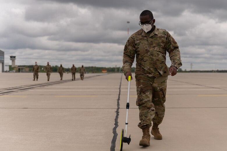 Airman walking with a measuring wheel.