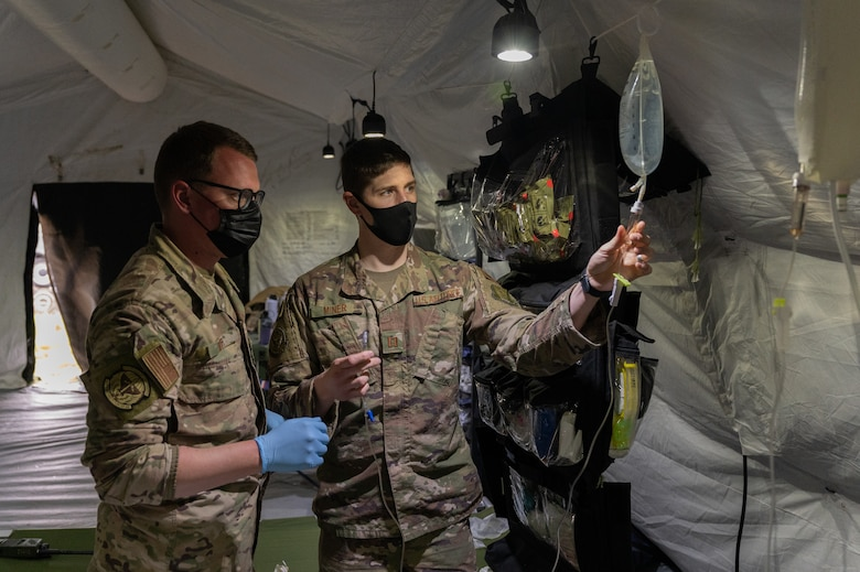 Two Airmen standing next to an IV.