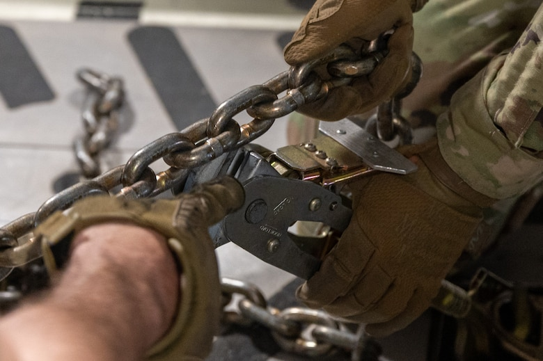 Close-up of hands securing chains.