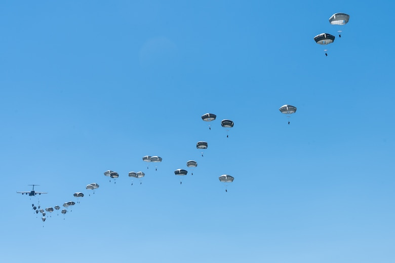 A trail of paratroopers behind an aircraft.