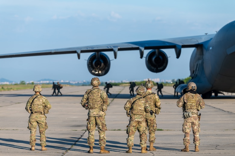 Airmen and Soldiers stand next to an aircraft on an airfield.