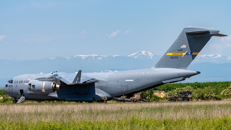 A aircraft sits on an airfield, while Airmen and Soldiers unload cargo.