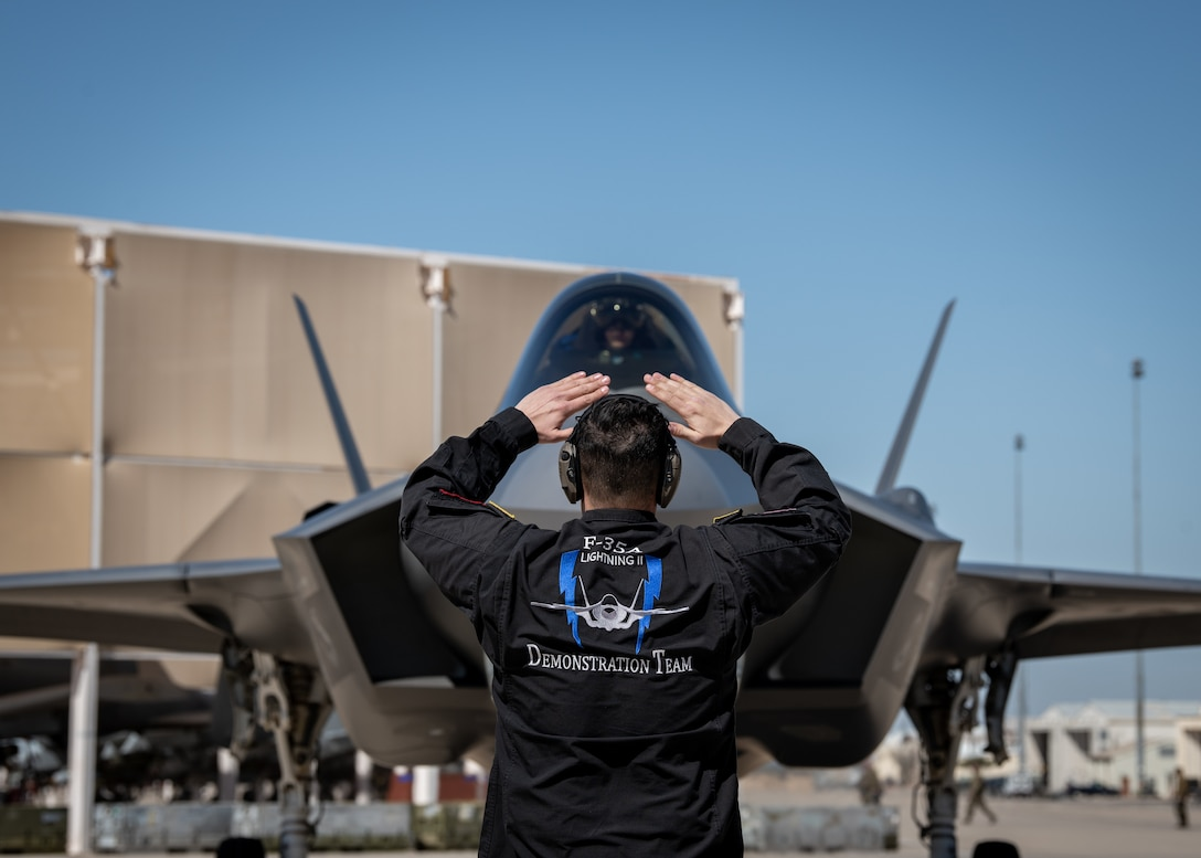An Air Force maintainer marshals in an F-35A Lightning II fighter jet.