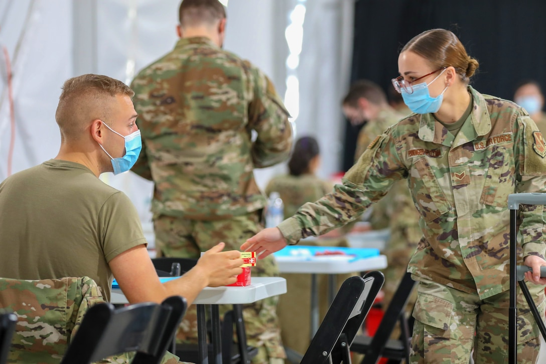 An airman wearing a face mask distributes medical supplies to an airman seated at a table wearing a face mask.
