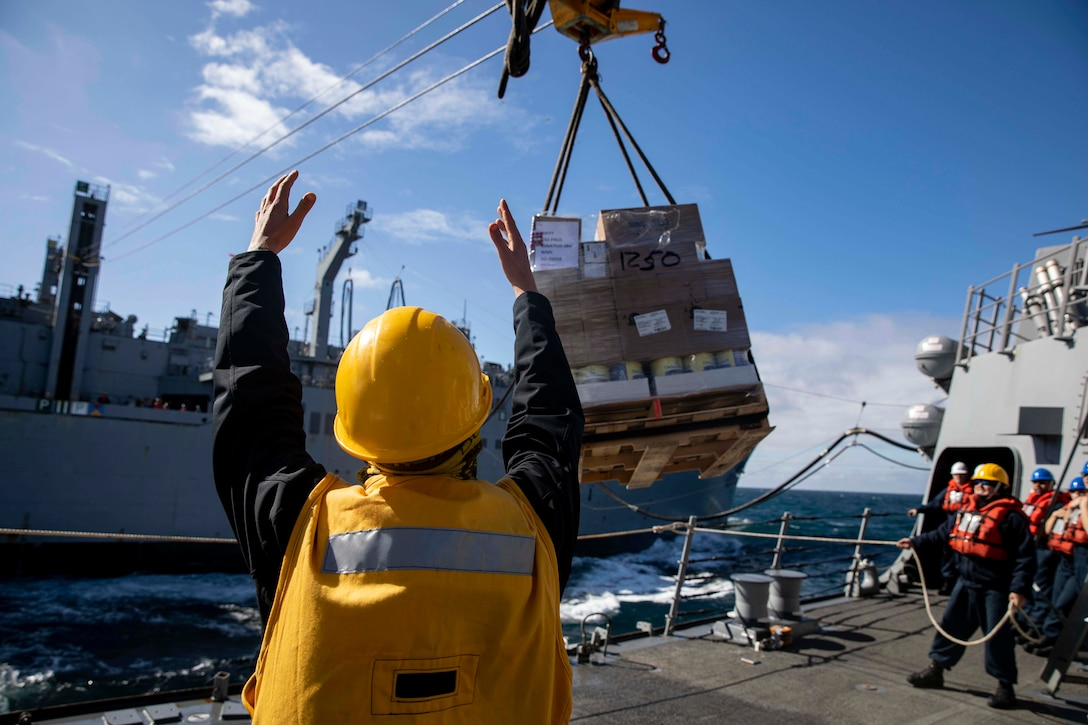 A man signals to a ship as a large container is lifted in the air with a pulley.