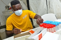 A servicemember sits in a yellow shirt in front of a table of red and blue testing vials. Covi