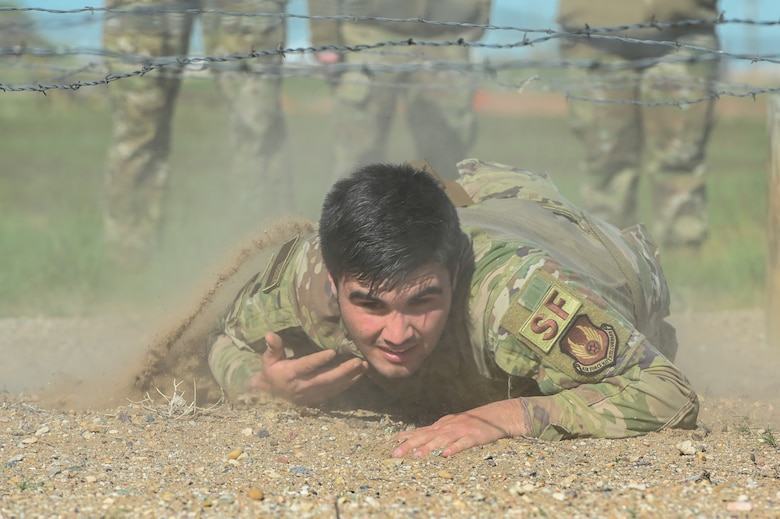 Airman 1st Class Wyatt Ramos, 75th Security Forces Squadron, crawls under barb wire during the National Police Week obstacle course competition May 11, 2021, at Hill Air Force Base, Utah. The obstacle course competition was one of many events 75th SFS hosted to commemorate the week to honor the sacrifices of the law enforcement community. (U.S. Air Force photo by Cynthia Griggs)