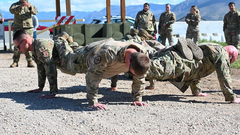 The non-commissioned officer team from the 75th Security Forces Squadron do a four-man push-up during the National Police Week obstacle course competition May 11, 2021, at Hill Air Force Base, Utah. The obstacle course competition was one of many events 75th SFS hosted to commemorate the week to honor the sacrifices of the law enforcement community. (U.S. Air Force photo by Cynthia Griggs)