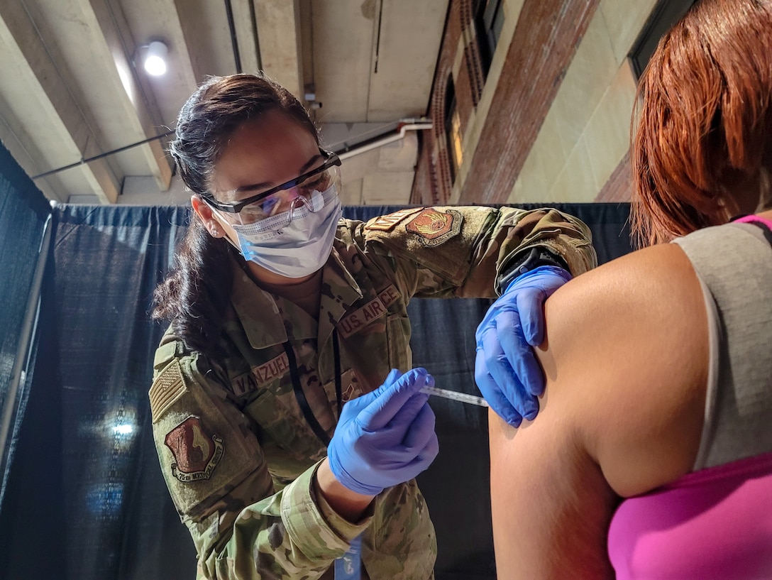 U.S. Airman 1st Class Pollyann Valenzuela, a Los Angeles native and medic with the 75th Medical Group stationed at Hill Air Force Base, Utah, assigned to 1st Detachment, 64th Air Expeditionary Group, administers a COVID-19 vaccination to a local community member at the state-run, federally-supported Ford Field COVID-19 Community Vaccination Center in Detroit, March 26, 2021. The Ford Field CVC is being supported by members of the Federal Emergency Management Agency, Henry Ford Health Systems, Michigan Department of Health, Meijer and the U.S. Air Force. U.S. Northern Command, through U.S. Army North, remains committed to providing continued, flexible Department of Defense support to FEMA as part of the whole-of-government response to COVID-19. (U.S. Army photo by Spc Andrew Wash, 5th Mobile Public Affairs Detachment)