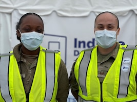 U.S. Air Force Airman First Class Taneia Thomas, left, and U.S. Air Force Staff Sgt. Saundra Turner, right, medical technicians with the 87th Medical Operations Squadron at McGuire Air Force Base, New Jersey, assigned to the 2nd Detachment, 64th Air Expeditionary Group, pose for a picture in between vaccinations at the state-led, federally supported Community Vaccination Center (CVC) at the former Roosevelt High School in Gary, Indiana, April 29, 2021.  In addition to administering vaccines, the medical professionals assigned to the CVC monitor the care of all patients, before and after each shot, in order to maintain site safety and respond to any adverse or situation. The CVC supports both drive-up and walk-in appointments and will vaccinate up to 3,000 local community members a day. U.S. Northern Command, through U.S. Army North, remains committed to providing continued, flexible Department of Defense support to the Federal Emergency Management Agency as part of the whole-of-government response to COVID-19. (U.S. Air Force photo by 2Lt Brittney Sturgis, 64th Air Expeditionary Group, 2nd Detachment.)