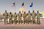 U.S. Airmen from the Wing Innovation Team stand in front of The Rock at Ali Al Salem Air Base, Kuwait, May 13, 2021. These Airmen, in various career fields across the installation, had helping hands in creating a product that automates about 90% of data scrubs unit travel representatives are required to do monthly. (U.S. Air Force photo by Senior Airman Taryn Butler)