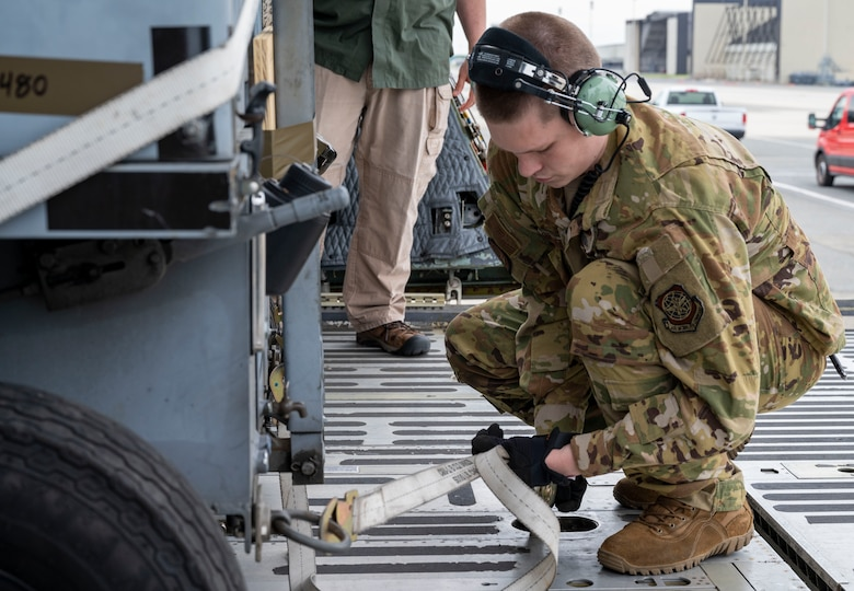 Airman 1st Class Joshua Grant, 9th Airlift Squadron loadmaster, secures cargo to the ramp of a C-5M Super Galaxy at Dover Air Force Base, Delaware, May 16, 2021. The aircraft departed in support of Exercise Mobility Guardian 2021, Air Mobility Command's largest and longest training event. Airmen are tested through a challenging, realistic and detailed scenario based on real-world challenges. More than 1,800 participants will operate 18 mobility aircraft at six locations in Michigan and Wisconsin during the exercise. (U.S. Air Force photo by Airman 1st Class Cydney Lee)