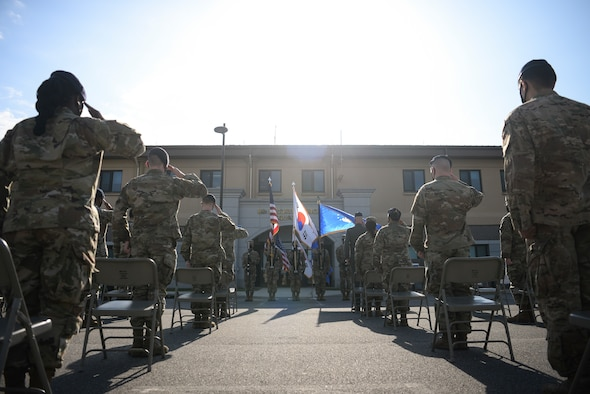 Airmen salute during a Police Week ceremony.