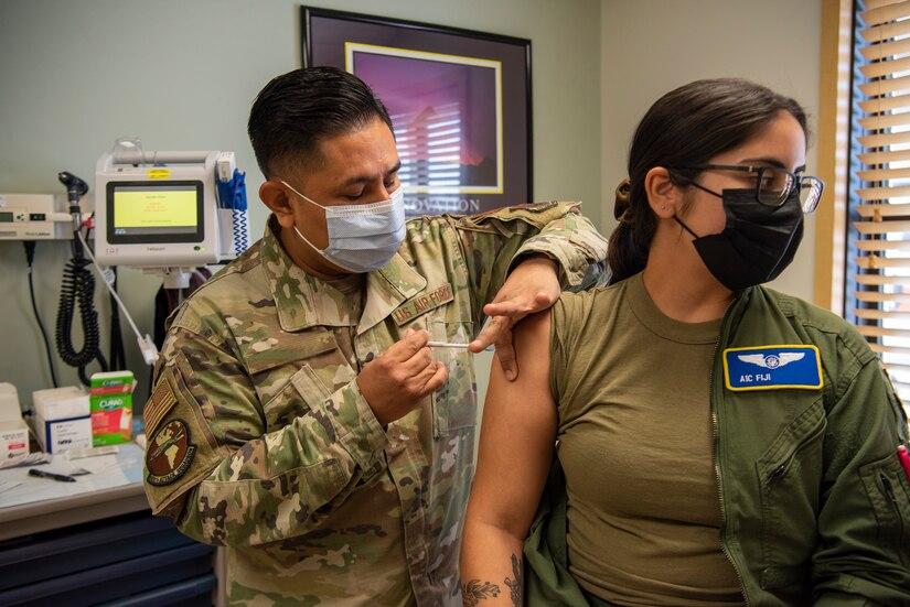 Tech Sgt. Benigno gives a COVID-19 vaccine shot to Airman 1st Class Fiji.