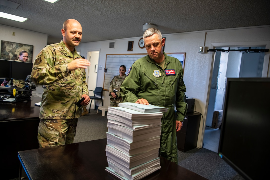 Two Airmen look at a large stack of paperwork from a recent trial.