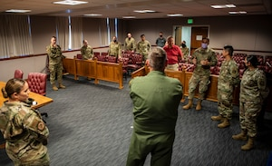 A group of people are in a courtroom listening to an Airmen brief leadership from the base.