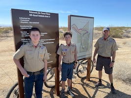 Lt. Col. Scott Fann, right, deputy commandant, U.S. Air Force Test Pilot School, along with son William Fann, center, and Allan Scott pose next to the new map and sign of the newly marked off-road trail at one of the trail heads on Edwards Air Force Base, California, during the grand opening, March 6.