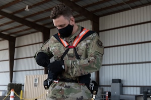 Airman 1st Class Kyle Sunderman, 60th Aerial Port Squadron ramp serviceman, dons Aerial Porter Exoskeleton equipment before demonstrating its capabilities May 14, 2021, at Travis Air Force Base, California. The Aerial Porter Exoskeleton is a piece of equipment designed to reduce strain when lifting various items. (U.S. Air Force photo by Senior Airman Cameron Otte)