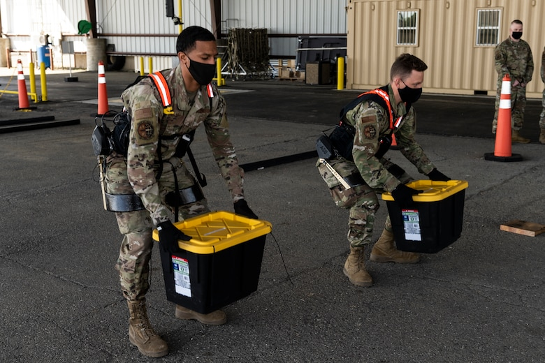 Airman 1st Class Xaviar Archangel, 60th Aerial Port Squadron aerial porter, and Airman 1st Class Kyle Sunderman, 60th APS ramp serviceman, showcase the capabilities of the Aerial Porter Exoskeleton May 14, 2021, at Travis Air Force Base, California. The Aerial Porter Exoskeleton is a piece of equipment designed to reduce strain when lifting various items. (U.S. Air Force photo by Senior Airman Cameron Otte)