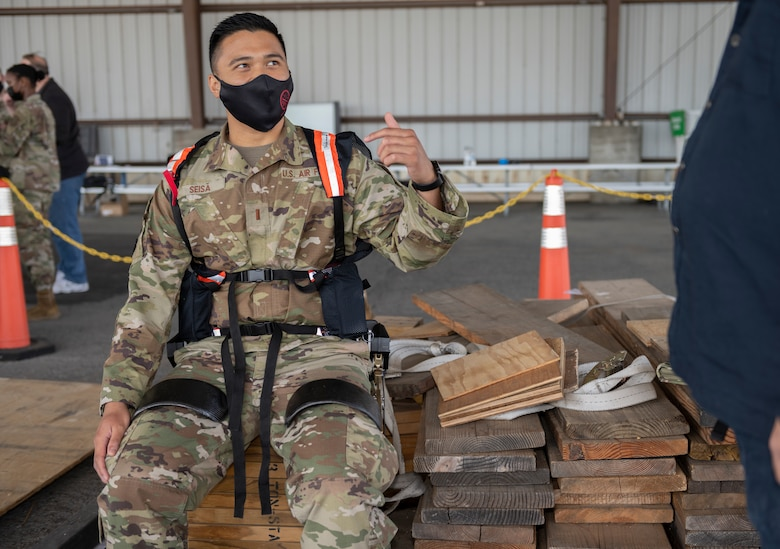 2nd Lt. Germaine Seisa, 60th Logistic Readiness Squadron officer in charge of vehicle management, tries on the Aerial Porter Exoskeleton May 14, 2021, at Travis Air Force Base, California. The Aerial Porter Exoskeleton is a piece of equipment designed to reduce strain when lifting various items. (U.S. Air Force photo by Senior Airman Cameron Otte)