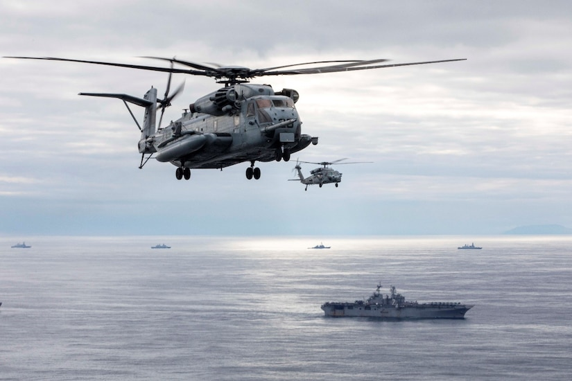 Helicopters fly alongside a ship in a vast ocean.