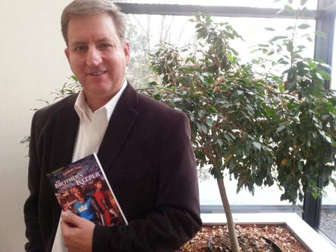 """David Wright, videographer for Arnold Engineering Development Complex, pictured in October 2018 with his first book """"My Brother's Keeper,"""" which was published in 2014. The book is part of a series called Galahad's Doom. The second book in the series, """"Marching as to War,"""" came out in 2018. Wright is currently working on the third and final book, which will be called """"The Armor of God."""" (Courtesy photo)"""