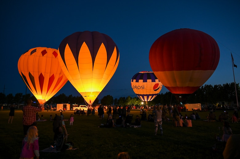 Hot air balloons light up the evening sky