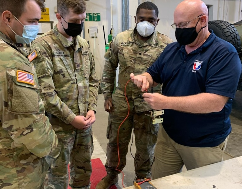 Russ Kropp, a U.S. Army Tank-automotive and Armaments Command employs Logistics Assistance Representative assigned to the 405th Army Field Support Brigade's Army Field Support Battalion-Germany, shows a group of Soldiers from the 92nd Military Police Company how to check a Humvee brake-torque converter cutout switch.