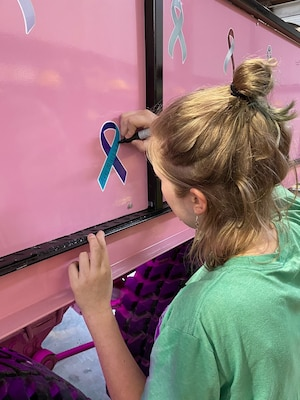 Girl in green shirt signs an awareness ribbon on a pink truck