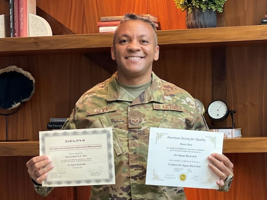 Staff Sgt. Denis Silva holds two certificates in front of a set of shelves.